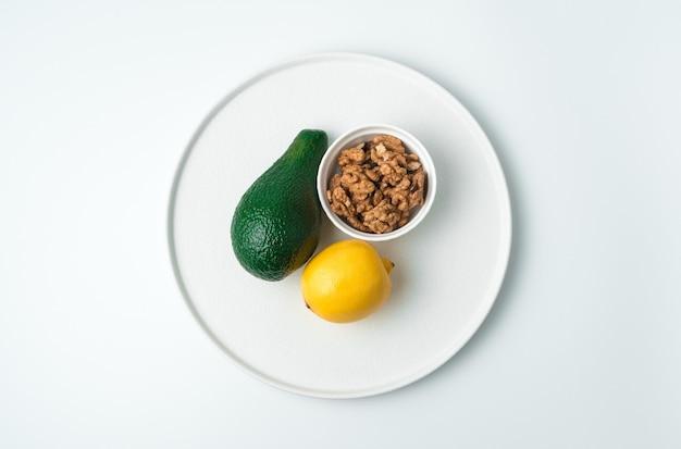 Plato blanco plano con aguacate y limón y nueces sobre un fondo blanco. vista superior con espacio para copiar. el concepto de alimentación saludable.