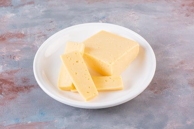 Plato blanco de rodajas de queso amarillo sobre superficie de mármol.