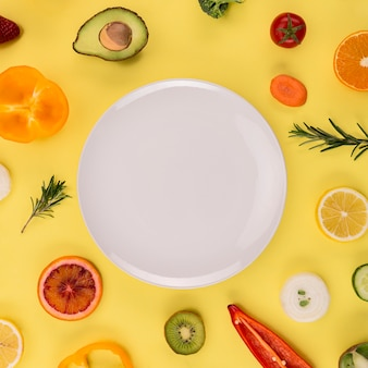 Plato blanco rodeado de verduras y frutas.