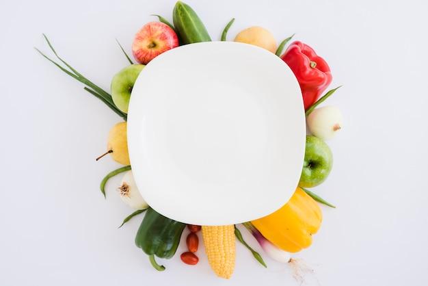 Plato blanco sobre el pepino; manzana; pimiento; cebolla; maíz y cebolletas sobre fondo blanco