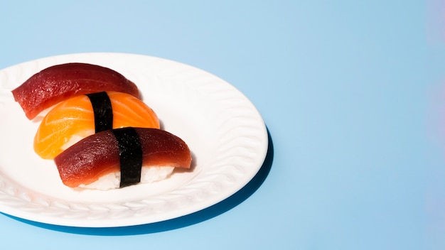 Plato blanco con sushi de atún y salmón sobre un fondo azul.
