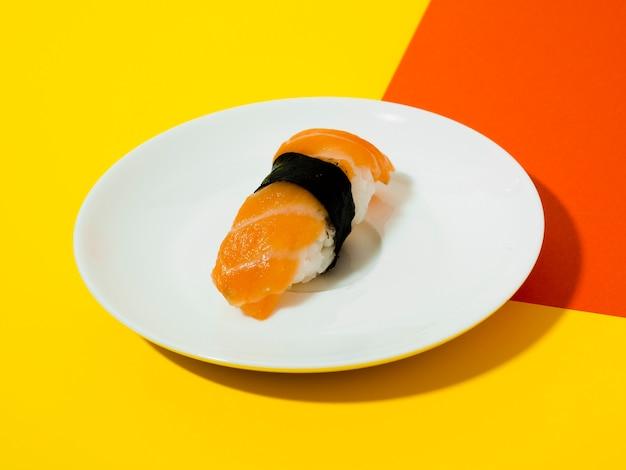 Plato blanco con sushi sobre un fondo amarillo y naranja