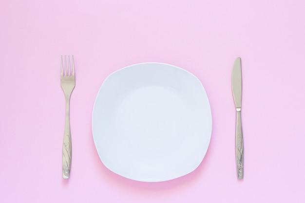 Plato blanco y tenedor, mesa-cuchillo sobre fondo rosa.