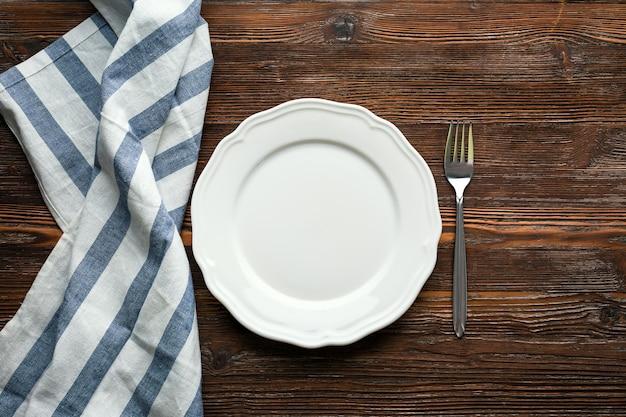 Plato blanco, tenedor y servilleta sobre un fondo de madera