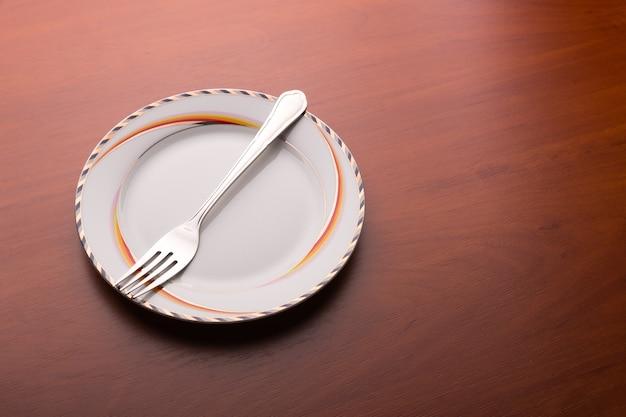 Plato blanco y tenedor sobre mesa de madera