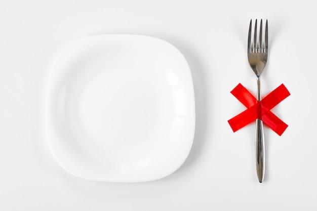 Plato blanco con tenedor con x cruz roja sobre la mesa. dieta, concepto de estilo de vida poco saludable