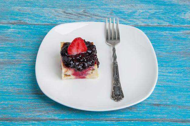 Plato blanco con un trozo de tarta de queso