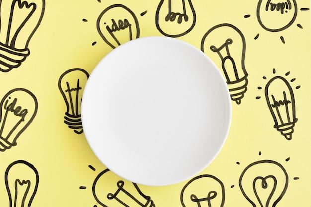 Plato blanco vacío en mano dibujado fondo bombilla