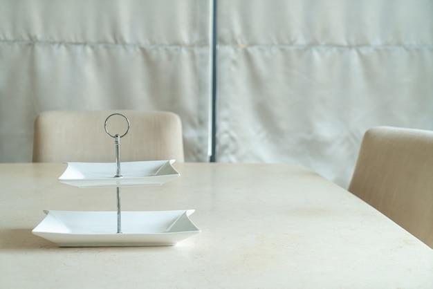 Plato blanco vacío en la mesa de comedor