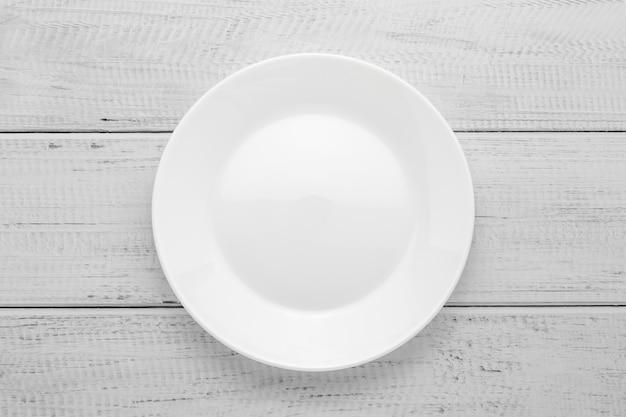 Plato blanco vacío en la mesa de madera gris. vista superior. fondo de tablero de madera.