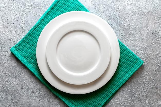 Plato blanco vacío servido en servilleta de alivio y fondo de hormigón gris en relieve. vista superior maqueta para menú