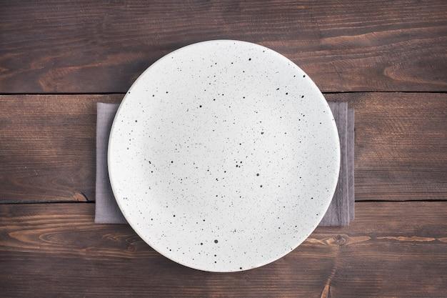 Plato blanco vacío sobre fondo rústico de madera. vista superior con espacio de copia.