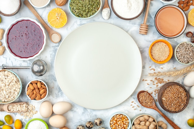 Plato blanco de vista superior cuencos con almendras semillas de maíz cacahuetes granos de trigo semillas de sésamo huevos palo de miel huevos de codorniz