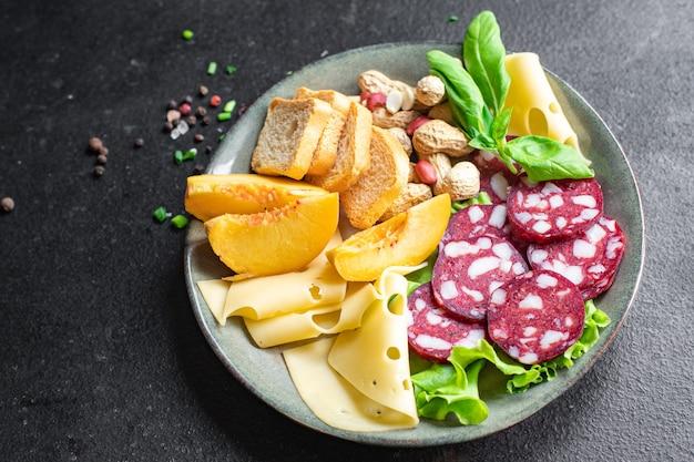 Plato de bocadillos de carne salchicha queso nueces melocotón fruta tostada pan ahumado o curado en seco bocadillo de comida