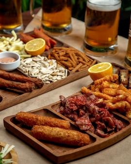 Plato de bocadillos de cerveza con pollo frito con queso y salchichas