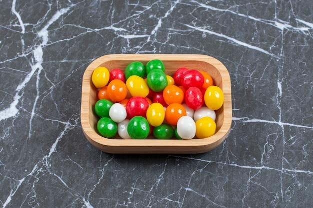Plato de caramelos de colores sobre mármol.