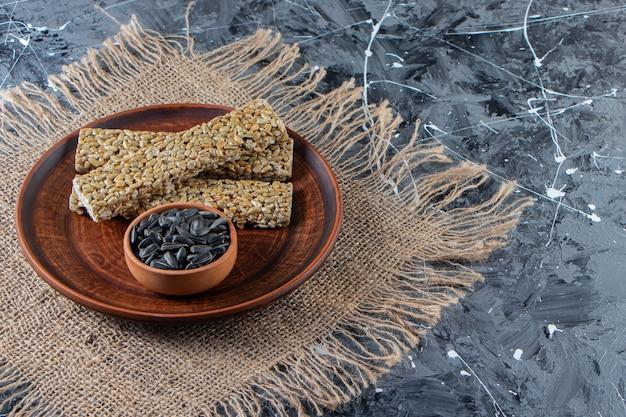 Plato de caramelos quebradizos con semillas de girasol sobre superficie de mármol.