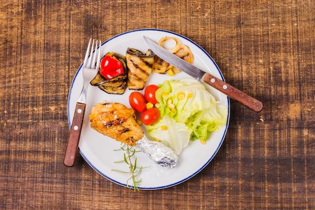 Plato con carne a la brasa y verduras crudas.