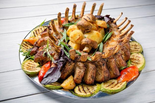 Plato de carne con deliciosos trozos de carne, ensalada, costillas, verduras a la parrilla y papas en la mesa de madera blanca