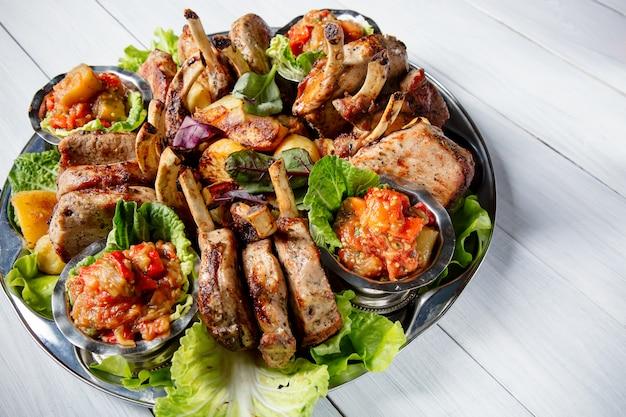 Plato de carne con deliciosos trozos de carne, ensalada, costillas, verduras a la parrilla, papas y salsa en la mesa de madera blanca