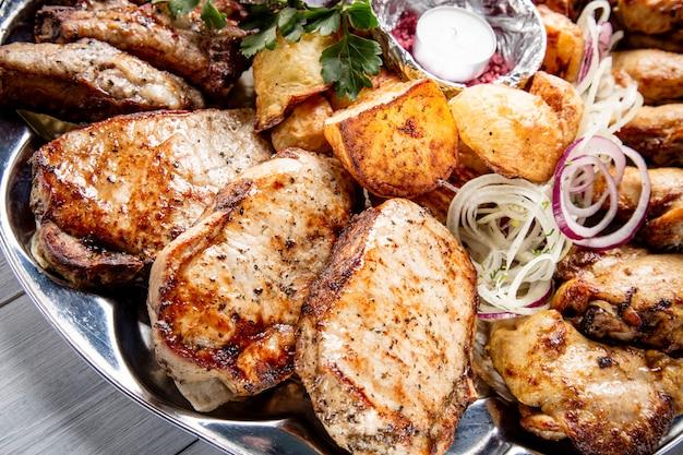 Plato de carne con deliciosos trozos de carne, papas, cebolla y velas en la mesa de madera blanca
