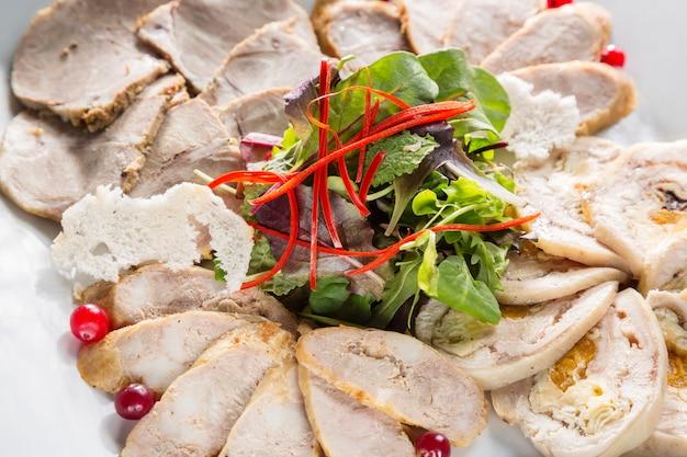 Plato de carne con deliciosos trozos de jamón en rodajas, pimienta, hierbas y carne con arándano