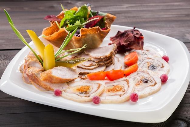 Plato de carne con deliciosos trozos de jamón en rodajas, tomates cherry, hierbas y carne con arándano