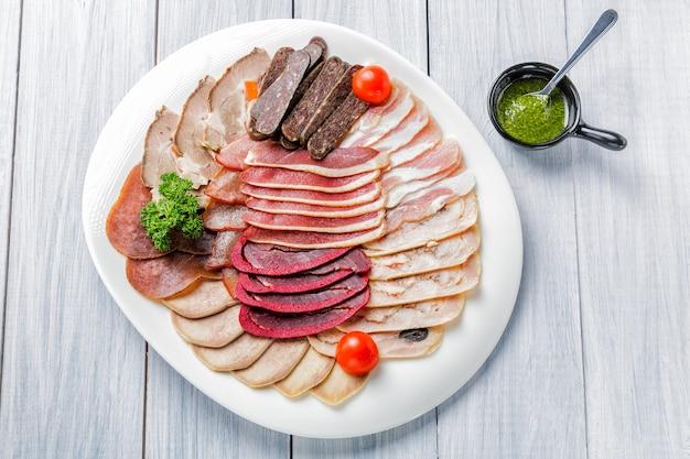 Plato de carne con deliciosos trozos de jamón en rodajas, tomates cherry, hierbas, carne y salsa.