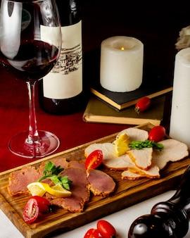 Plato de carne con rodajas de tomate y limón servido con vino