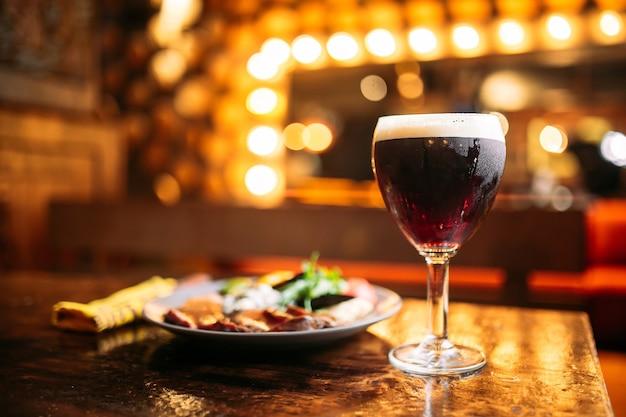 Plato de carne y verduras cocidas con un vaso de cerveza oscura con luces borrosas