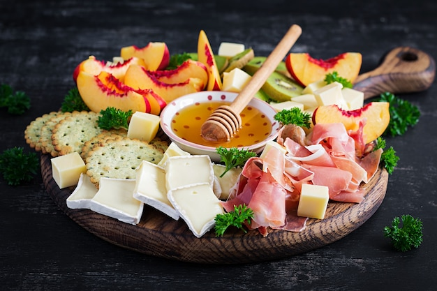 Plato de catering de antipasto italiano con jamón, queso y fruta sobre un fondo oscuro.