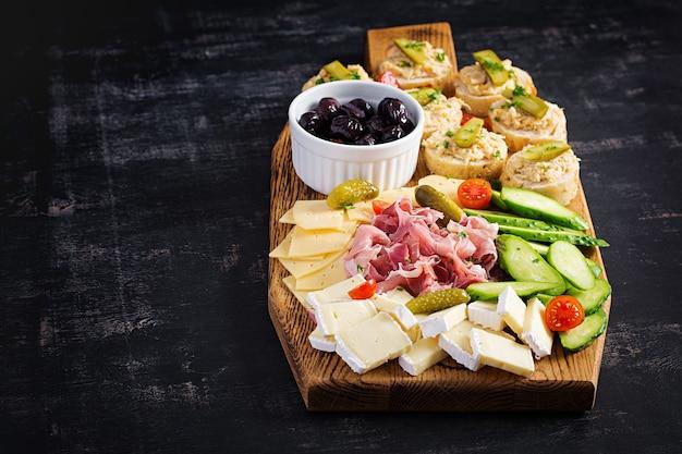 Plato de catering de antipasto con jamón, queso, canapé y aceitunas negras sobre una tabla de madera. vista superior, arriba