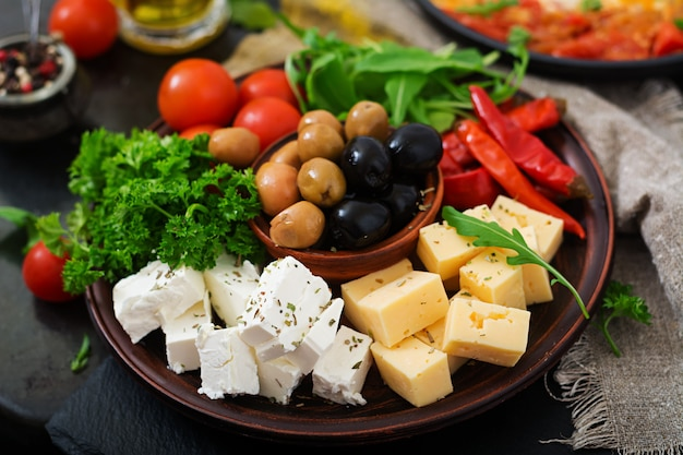 Plato de cena con aceitunas, queso y verduras.