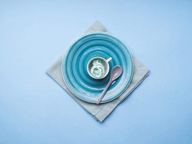 Plato de cerámica azul en servilleta con flores