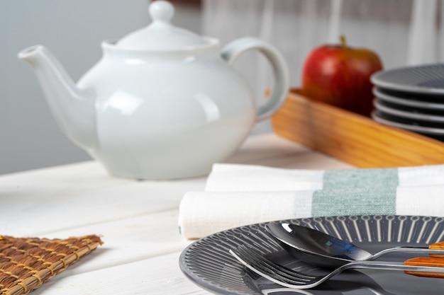 Plato de cerámica gris brillante con cubiertos en la mesa de cocina de madera