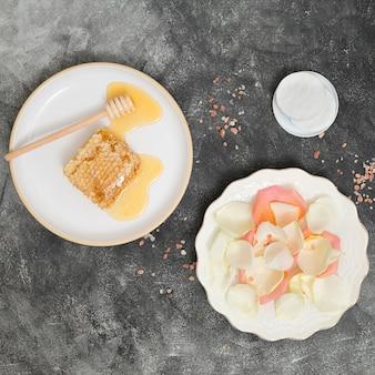 Plato cerámico blanco con nido de abeja; cucharón y pétalos de rosa con almohadillas de algodón redondas blancas sobre fondo de hormigón negro