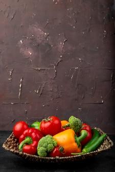 Plato de cesta lleno de verduras sobre superficie negra