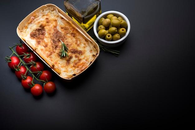 Plato clásico italiano de lasaña con tomate y oliva.