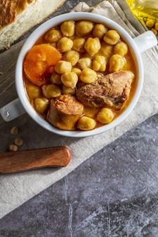Plato de cocido de garbanzos (cocido madrileño). con ternera, chorizo, bacon, zanahoria y aceite de oliva. dieta mediterránea. aspecto casero. vista superior con espacio de copia.