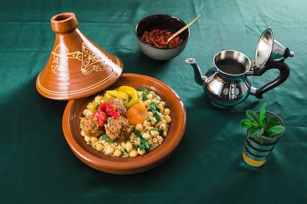 Plato con comida cerca de frutos secos, taza de bebida y tetera.