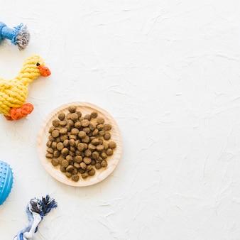 Plato con comida cerca de juguetes para mascotas