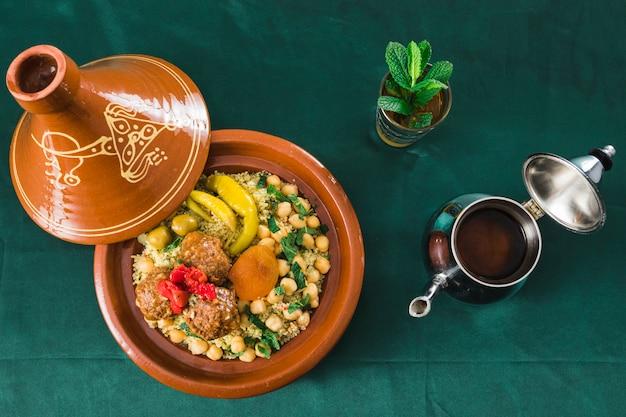 Plato con comida cerca de taza de bebida y tetera