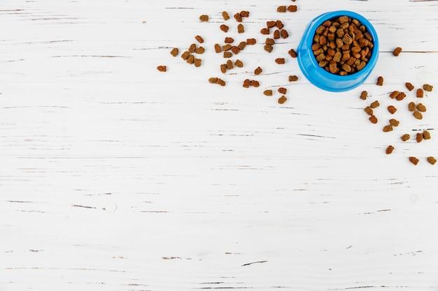 Plato de comida para mascotas en superficie de madera blanca