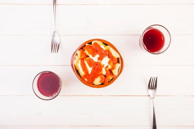 Plato con tenedores y bebidas en la mesa