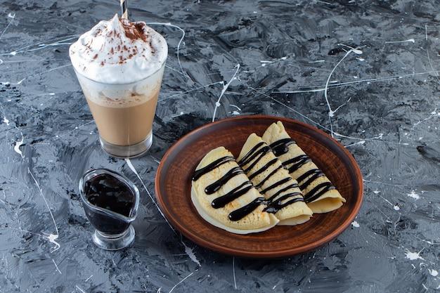 Plato de crepas caseras con cobertura de chocolate y vaso de café.
