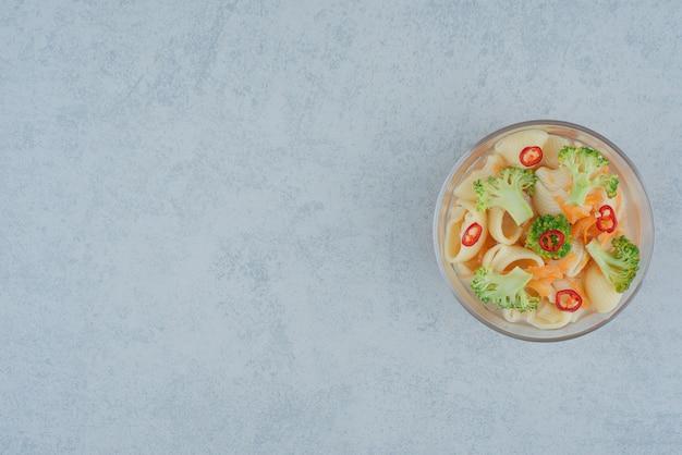 Un plato de cristal de macarrones y brócoli sobre fondo blanco. foto de alta calidad