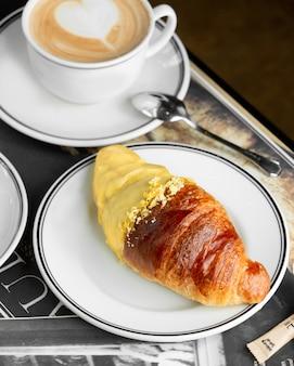 Plato de croissant medio sumergido en crema de vainilla