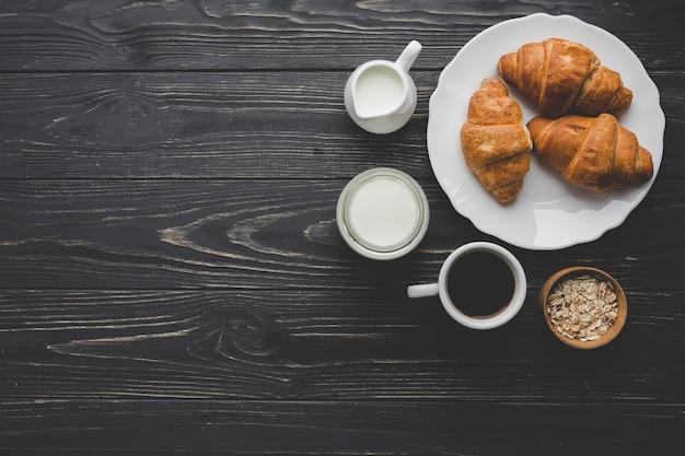 Plato con cruasanes cerca de café y productos lácteos