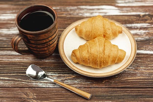 Con el plato con cruasanes y una taza de café sobre la mesa