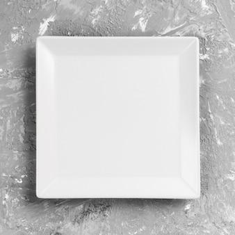Plato cuadrado blanco sobre mesa gris. vista de perspectiva